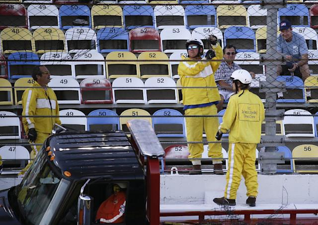 Track workers repair a hole in the safety fence along the front stretch caused by a wreck during practice for the Daytona 500 NASCAR auto race at Daytona International Speedway in Daytona Beach, Fla., Wednesday, Feb. 19, 2014. (AP Photo/John Raoux)