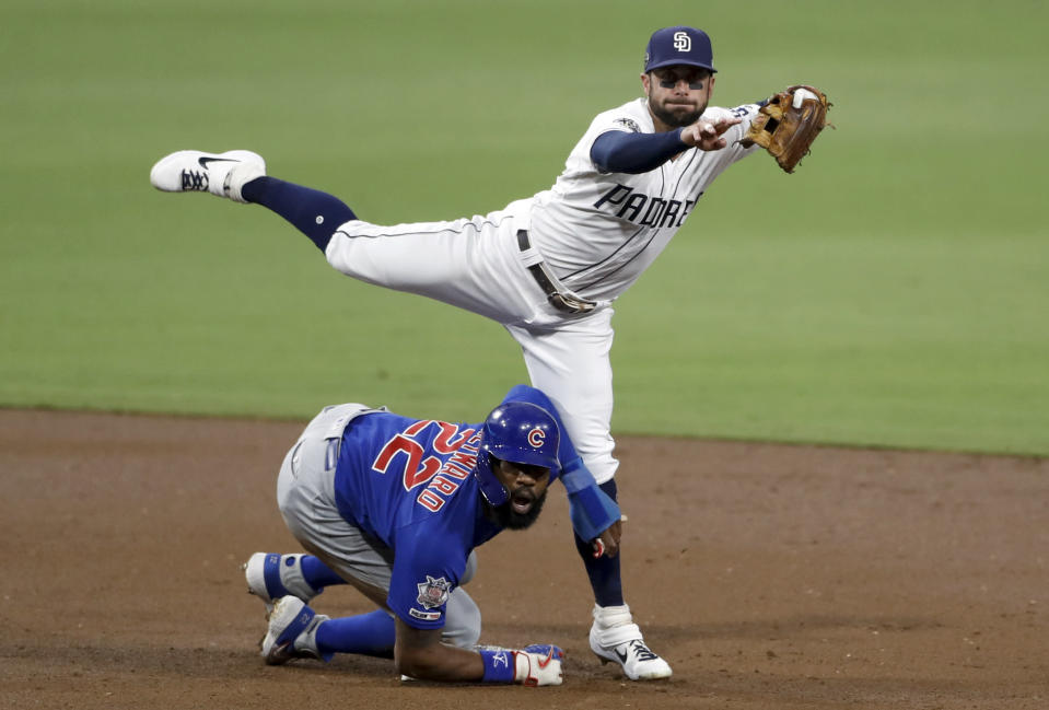 San Diego Padres second baseman Greg Garcia, above, watches his throw to first as Chicago Cubs' Jason Heyward (22) arrives late to second during the second inning of a baseball game Monday, Sept. 9, 2019, in San Diego. Chicago Cubs' Kyle Hendricks was safe at first on the play. (AP Photo/Gregory Bull)