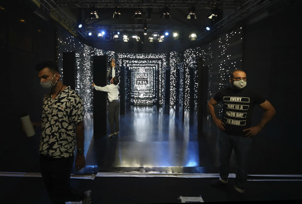 A worker sets the stage for the Lotus make-up India Fashion week digital show in New Delhi, India, Friday, Oct. 2, 2020. India's first digital fashion week is being held from Oct. 14-18, live streaming the spring-summer collections by more than 40 fashion designers under the banner of Lotus Make-up India Fashion Week. Not to miss the October deadline, the Fashion Design Council of India converted parts of its office building into a studio in a bustling industrial area of Delhi. It created a stage, screens and bespoke lighting to facilitate shooting of fashion films and videos by the designers. (AP Photo/Manish Swarup)