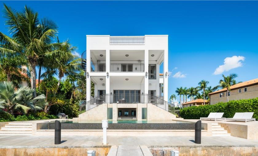 The half-acre property includes a three-story home, one-bedroom guesthouse, pool with a swim-up bar and concrete dock.