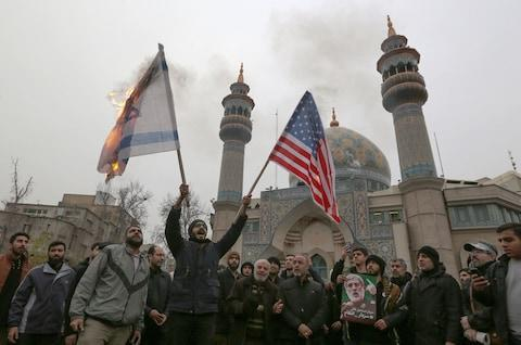 Iranians in Tehran burn an Israeli and a US flag during an anti-US protest over the killings during a US air strike of Iranian military commander Qassem Soleimani - Credit: AFP