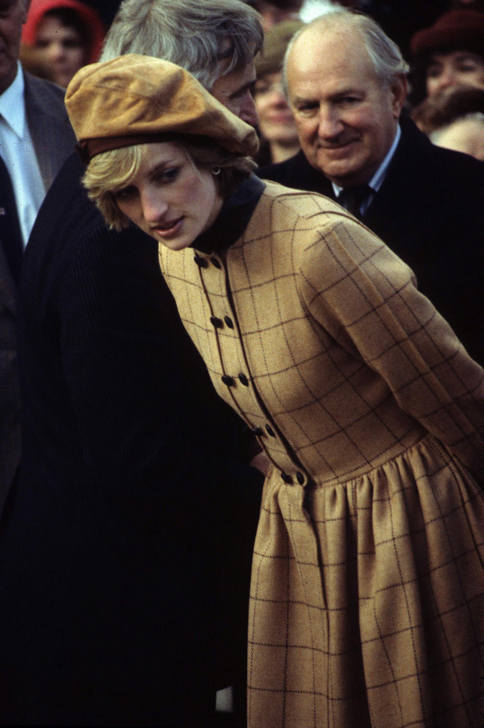 <p>A trend which has made a comeback this season, the beret. Here, Princess Diana tucks her side fringe beneath a brown beret which she wears with a button-up checked coat.<br><em>[Photo: PA]</em> </p>