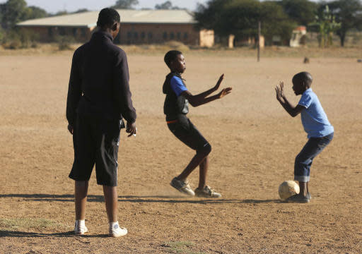 Double amputee and soccer coach, Tebogo Mofokeng, left, keeps an eye on his players during a training exercise in Winterveldt, South Africa, Sunday, June 17, 2018. Mofokeng's legs were amputated when he was a toddler but that didn't stop him fulfilling his dream of coaching young children. (AP Photo/Denis Farrell)
