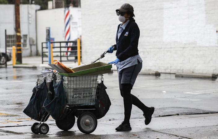 A U.S. Postal Service worker wears a mask and gloves