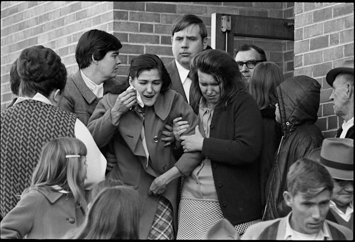 A grieving woman is lead away at the funeral of one of the miners killed in the Hurricane Creek explosion in Hyden, Ky. 1971