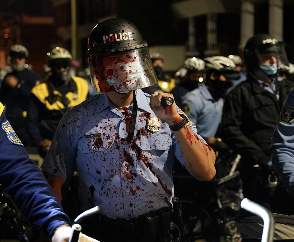 A blood splattered police officer seen holding a baton in Philadelphia riots.