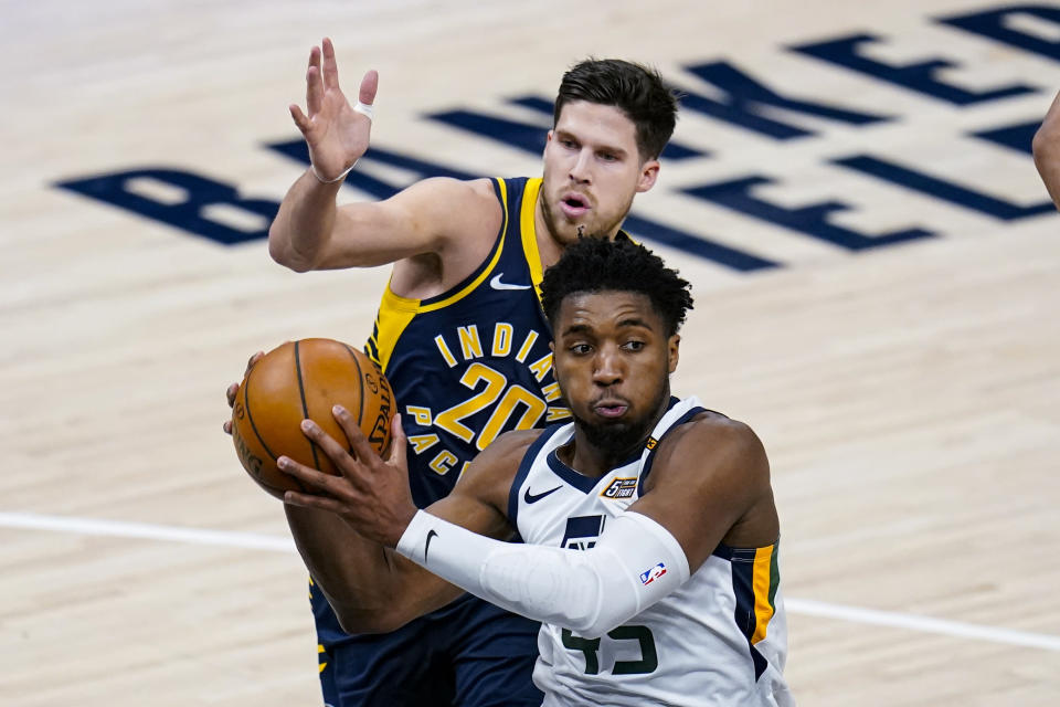 Utah Jazz guard Donovan Mitchell (45) makes a pass in front of Indiana Pacers forward Doug McDermott (20) during the first half of an NBA basketball game in Indianapolis, Sunday, Feb. 7, 2021. (AP Photo/Michael Conroy)
