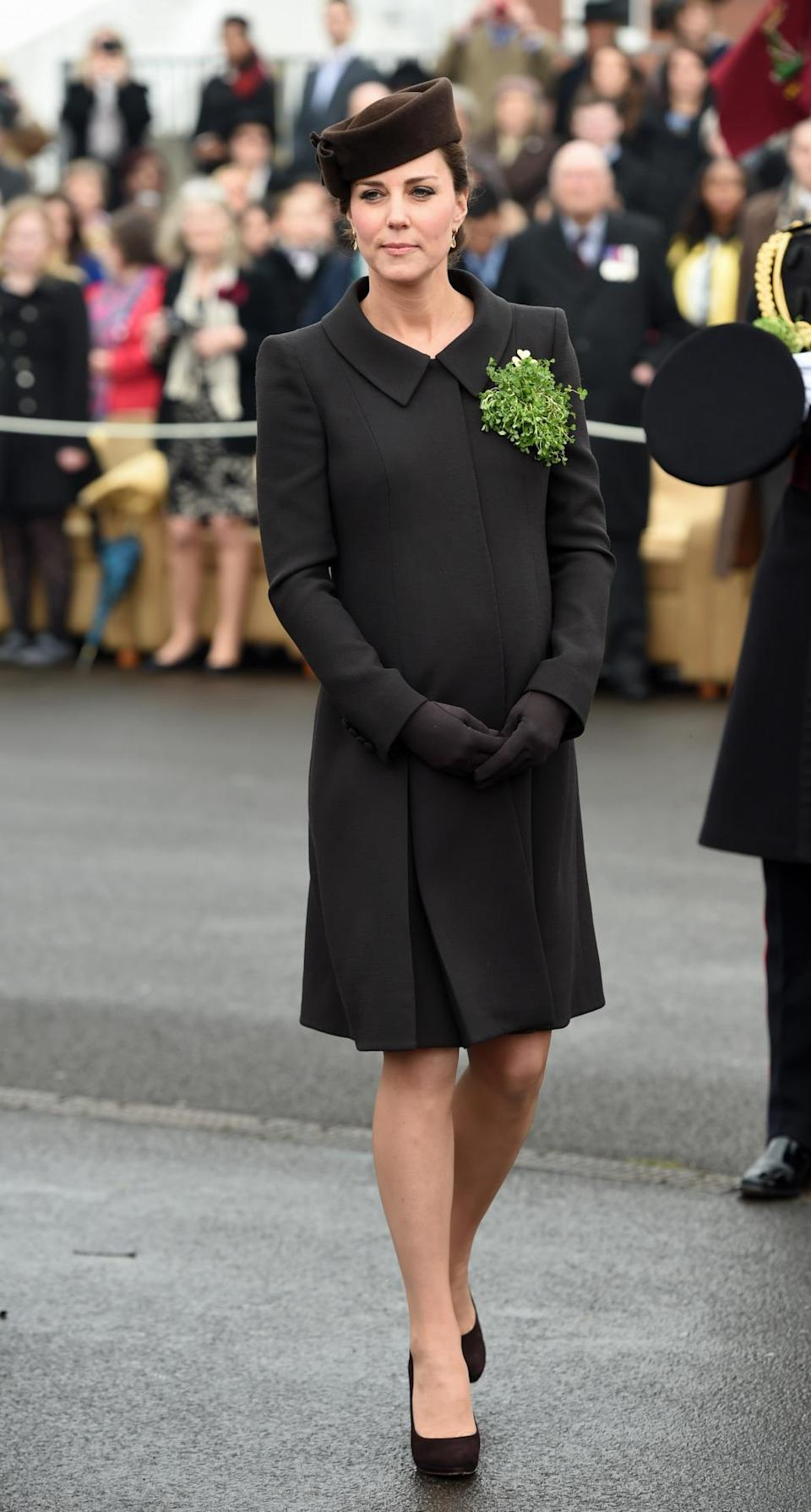 <p>Catherine Walker designed Kate's brown coat for the annual St. Patrick's Day parade. The Duchess accessorised with chocolate brown heels and bag by Emmy London and a matching Lock & Co hat.</p><p><i>[Photo: PA]</i></p>
