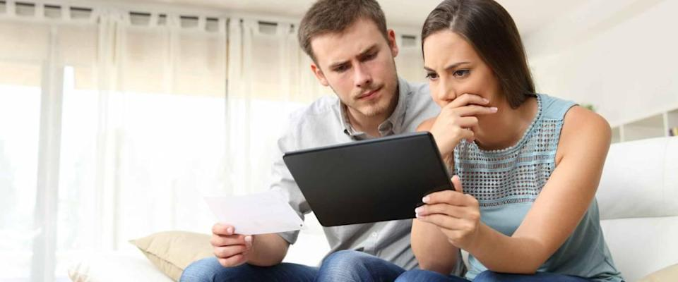 Worried couple checking bank account trouble online in a tablet sitting on a couch in the living room at home