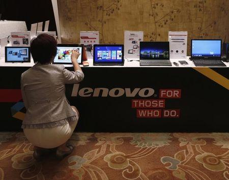 A woman tries a Lenovo tablet on display during a news conference announcing the company's annual results in Hong Kong May 21, 2014.