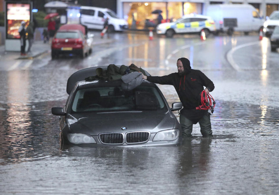 A man gathers items from a car along a flooded street, Thursday, Nov. 7, 2019, in Sheffield, England, after torrential fell rain in the area. (Danny Lawson/PA via AP)