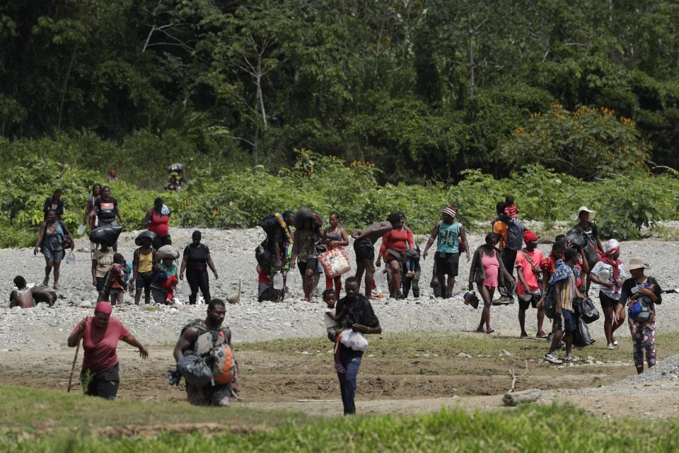 Migrants cross the Tuquesa River after a trip on foot through the jungle to Bajo Chiquito, Darien province, Panama, Wednesday, Feb. 10, 2021. Panama reopened its border in late January and ever since groups have been walking out of the dense Darien jungle that divides Panama and Colombia. (AP Photo/Arnulfo Franco)