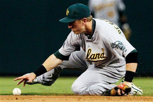 Oakland Athletics shortstop Cliff Pennington attempts to recover a ball that he bobbled off the bat of Texas Rangers' Ian Kinsler in the first inning of a baseball game, Monday, Sept. 24, 2012, in Arlington, Texas. Kinsler was safe at first with a single. (AP Photo/Tony Gutierrez)