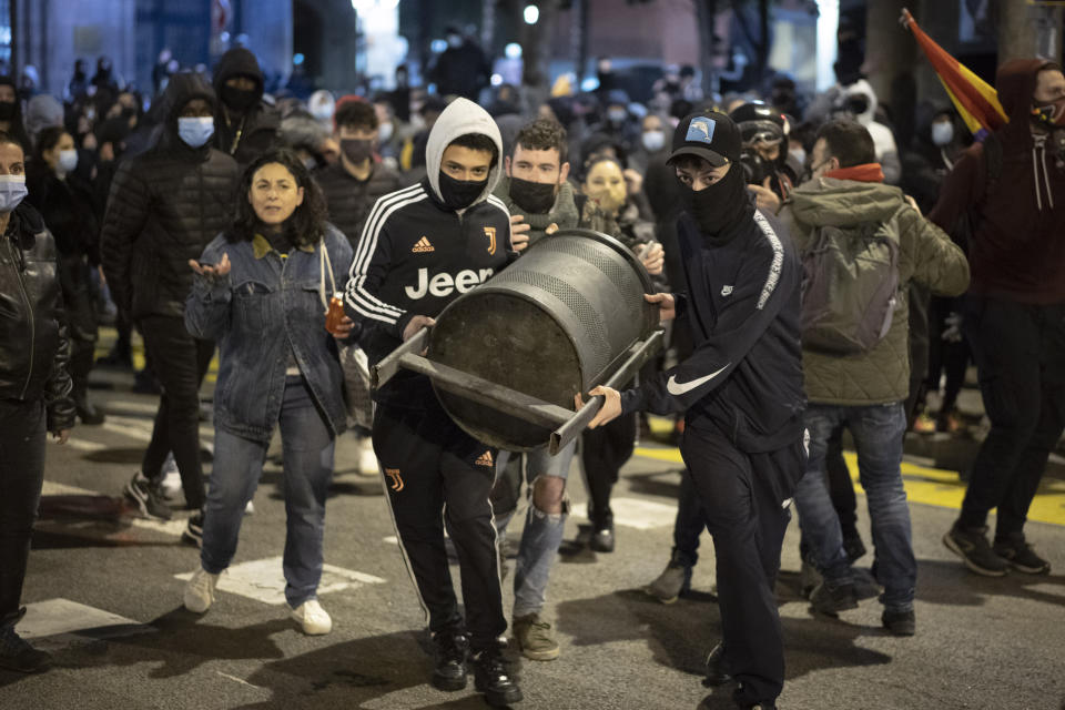 Demonstrators carry a rubbish bin to throw towards police officers protecting a national police station during clashes following a protest condemning the arrest of rap artis Pablo Hasél in Barcelona, Spain, Sunday, Feb. 21, 2021. The imprisonment of a rap artist for his music praising terrorist violence and insulting the Spanish monarchy has set off a powder keg of pent-up rage this week in Spain. The arrest of Pablo Hasél has brought thousands to the streets for different reasons. The majority march under the banner of freedom of speech, but Hasél's lyrics also tap into a debate about the role of Spain's parliamentary monarchy after financial scandals involving the royal house. (AP Photo/Emilio Morenatti)