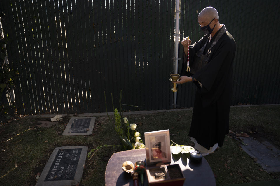 Shumyo Kojima, a head priest of Zenshuji Buddhist Temple, sprinkles purifying water over the grave of Giichi Matsumura during a memorial service at Woodlawn Cemetery in Santa Monica, Calif., Monday, Dec. 21, 2020. Giichi Matsumura, who died in the Sierra Nevada on a fishing trip while he was at the Japanese internment camp at Manzanar, was reburied in the same plot with his wife 75 years later after his remains were unearthed from a mountainside grave. (AP Photo/Jae C. Hong)