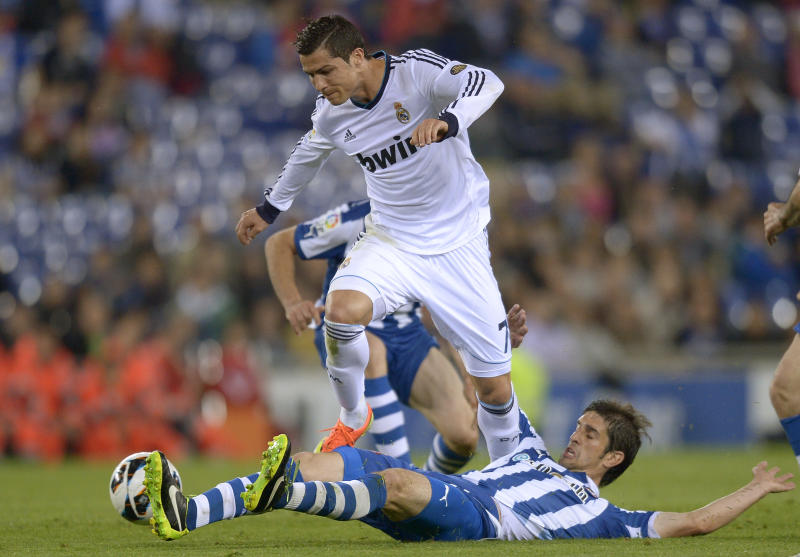Real Madrid's Cristiano Ronaldo, from Portugal, left, duels for the ball against Espanyol's Jordi Forlin, right, during a Spanish La Liga soccer match at Cornella-El Prat stadium in Cornella Llobregat, Spain, Saturday, May 11, 2013. (AP Photo/Manu Fernandez)