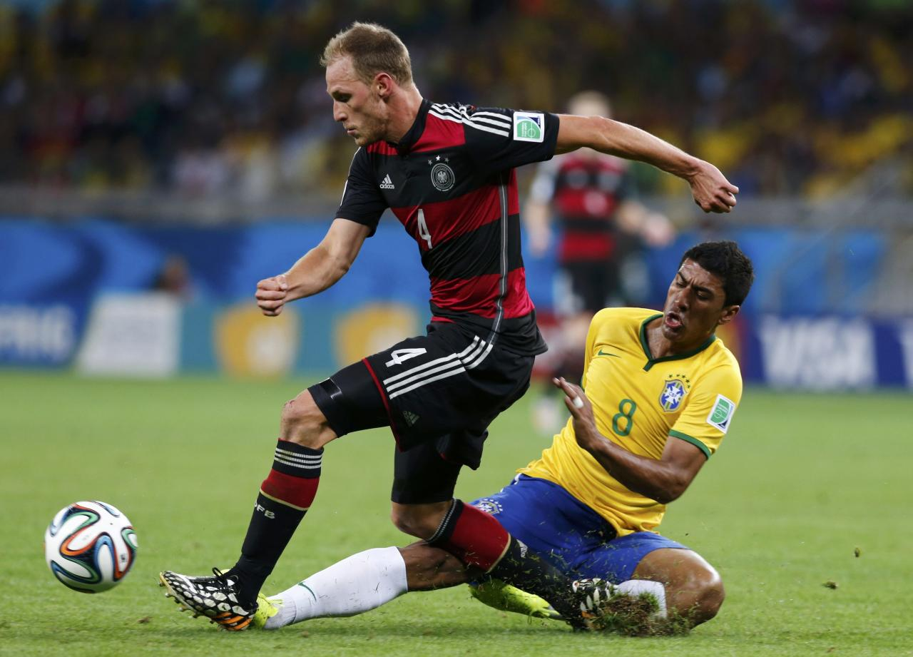 Germany's Benedikt Hoewedes fights for the ball with Brazil's Paulinho during their 2014 World Cup semi-finals at the Mineirao stadium in Belo Horizonte July 8, 2014. REUTERS/Marcos Brindicci (BRAZIL - Tags: SOCCER SPORT WORLD CUP)