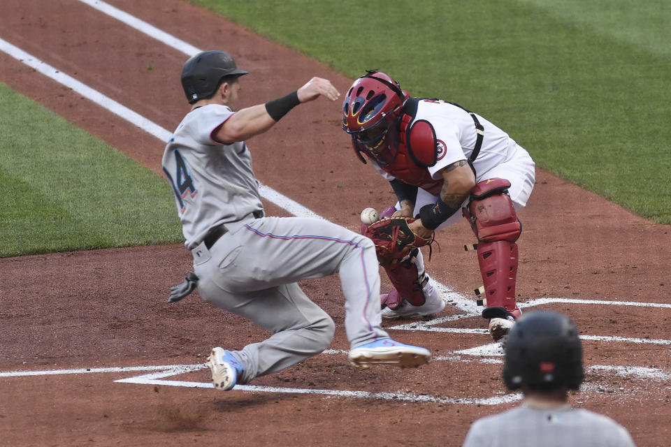St. Louis Cardinals catcher Yadier Molina, right, attempts to tag out Miami Marlins right fielder Adam Duvall during the second inning of a baseball game Monday, June 14, 2021, in St. Louis. (AP Photo/Joe Puetz)