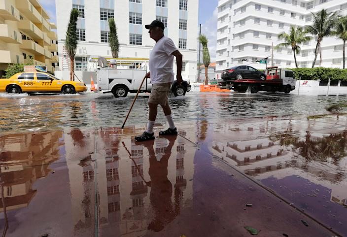 Louis Fernandez walks along a flooded Collins Avenue in Miami Beach, Fla. in 2015. (Photo: Lynne Sladky/AP)