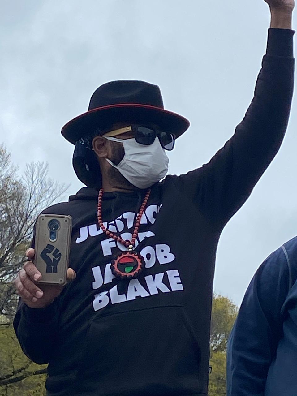 a man with a mask and a hat and a sweatshirt that says justice for jacob blake raises his fist