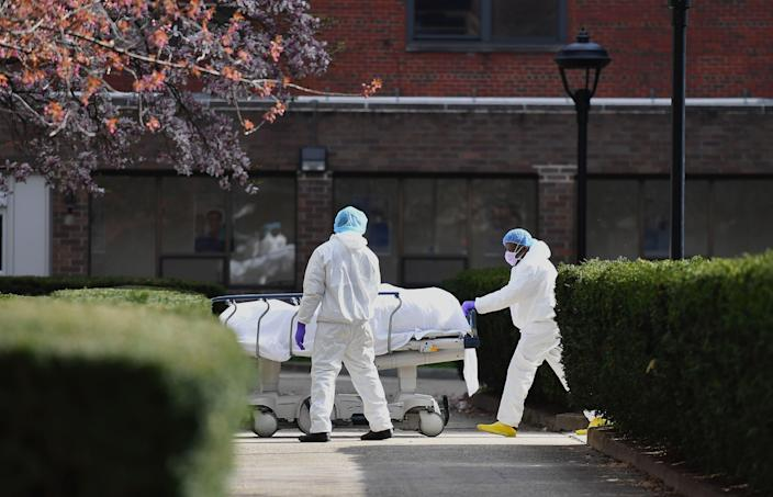 Medical personnel wearing personal protective equipment transport the body of a deceased patient from a refrigerated truck to Kingsbrook Jewish Medical Center on April 8, 2020 in Brooklyn, New York.
