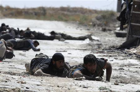 Free Syrian Army fighters take cover from snipers by crawling on the front line in Aleppo's Sheikh Saeed neighbourhood September 21, 2013. REUTERS/Molhem Barakat