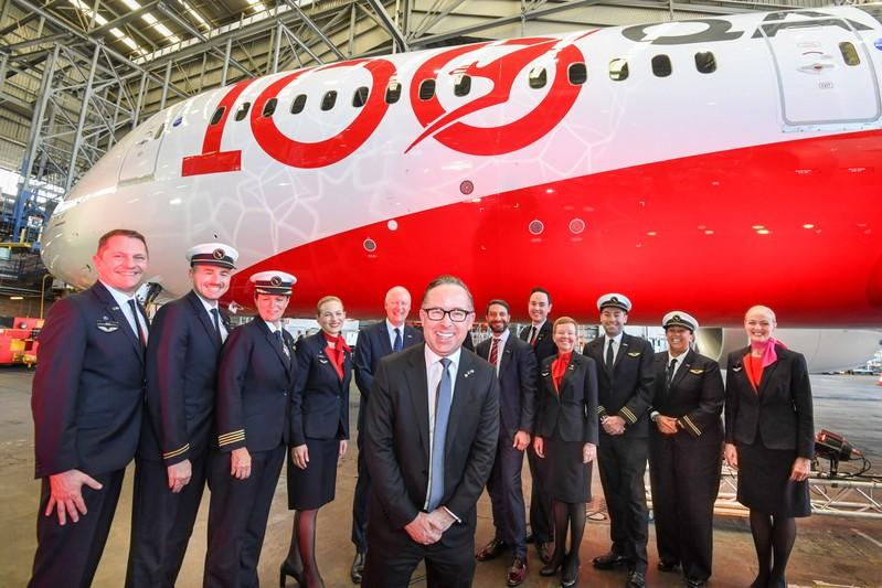 Qantas CEO Alan Joyce (centre) poses with the crew of QF7879, which flew direct from London to Sydney, during the Qantas Centenary Launch at Qantas Sydney Jet Base in Sydney