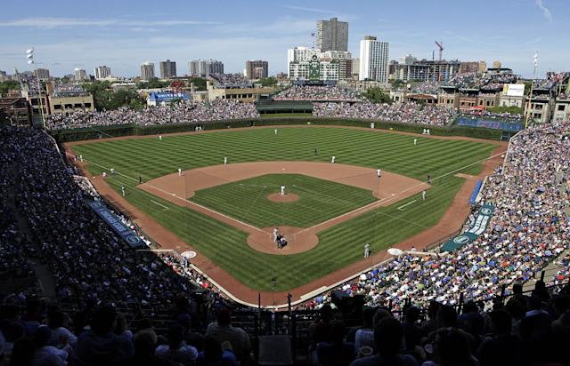 FILE - In this Aug. 4, 2013, file photo, the Los Angeles Dodgers play the Chicago Cubs at Wrigley Field in Chicago. Wrigley Field has been the site of so much heartbreak that some fans who spend their whole lives waiting for a winner ask their families, if they can pull it off, to sneak their ashes inside to be scattered in the friendly confines _ a final resting place to keep on waiting. But before years turned into decades and decades turned into a century without a World Series title, Wrigley Field was in first time and time again in changing the way we watch baseball and the experience for fans in ballparks around the country. The historic ballpark will celebrate it's 100th anniversary on April 23, 2014. (AP Photo/Kiichiro Sato, File)