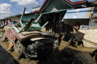 A man carries a cabinet past a broken car at the typhoon-damaged Kasiglahan village in Rodriguez, Rizal province, Philippines on Friday, Nov. 13, 2020. Thick mud and debris coated many villages around the Philippine capital Friday after Typhoon Vamco caused extensive flooding that sent residents fleeing to their roofs and killing dozens of people. (AP Photo/Aaron Favila)