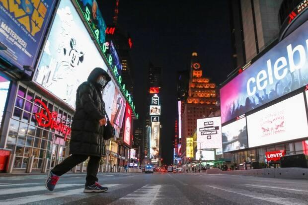 A person in a face mask walks through an almost empty Times Square in New York City as the COVID-19 outbreak pandemic continues.