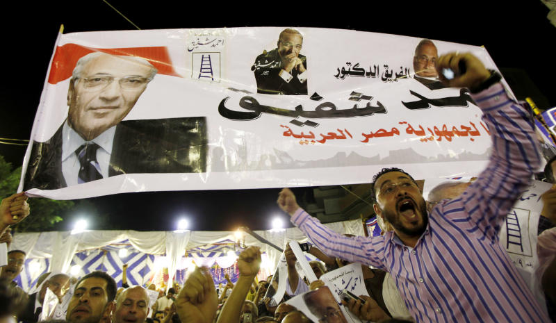 """Supporters of Egyptian presidential candidate Ahmed Shafiq chant slogans under a banner with his photos and Arabic writing which reads """"D. Ahmed Shafiq, Egypt's president,"""" during a rally in Tanta, about 90 Kilometers (56 miles) north of Cairo, Egypt, Friday, May 11, 2012. (AP Photo/Khalil Hamra)"""