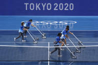 Workers push water off of a court during a rain delay in the tennis competition at the 2020 Summer Olympics, Tuesday, July 27, 2021, in Tokyo, Japan. (AP Photo/Patrick Semansky)