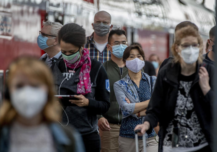 Passengers with face masks arrive in the main train station in Frankfurt, Germany, Thursday, Aug. 27, 2020. An announcement of German Chancellor Angela Merkel about the further strategy to avoid the outspread of the Coronavirus is expected later today. (AP Photo/Michael Probst)