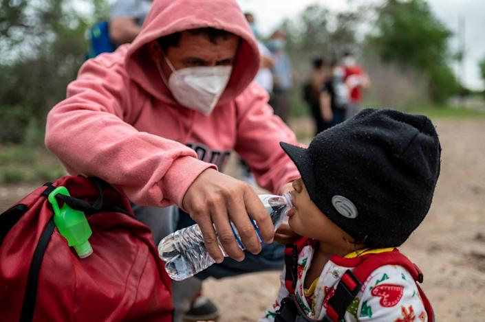 Nelson Alexsi Portillo Guillen gives his daughter Maria Amparo age 2, a drink of water, after being apprehended near the border between Mexico and the United States in Del Rio, Texas on May 16, 2021. / Credit: SERGIO FLORES/AFP via Getty Images