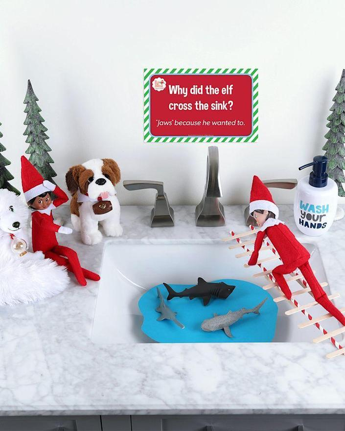 """<p>""""Why did the elf cross the sink?"""" reads the cute sign over this adventure. """"'Jaws' because he wanted to!""""</p><p><strong>Get the tutorial at <a href=""""https://elfontheshelf.com/elf-ideas/bridge-to-safety/"""" rel=""""nofollow noopener"""" target=""""_blank"""" data-ylk=""""slk:Elf on the Shelf"""" class=""""link rapid-noclick-resp"""">Elf on the Shelf</a>.</strong> </p>"""