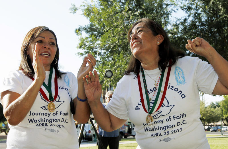 Rosa Maria Soto, right, and Maria Durand, both from Arizona, cheer as they react to the United States Supreme Court decision regarding Arizona's controversial immigration law, SB1070, comes down at the Arizona Capitol Monday, June 25, 2012, in Phoenix. The Supreme Court struck down key provisions of Arizona's crackdown on immigrants Monday but said a much-debated portion on checking suspects' status could go forward. (AP Photo/Ross D. Franklin)