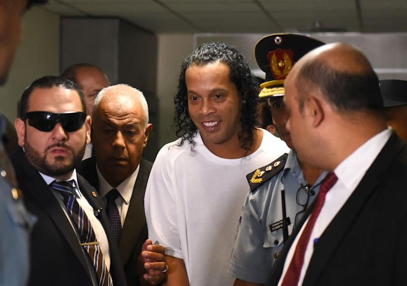 Brazilian retired football player Ronaldinho (C) arrives at Asuncion's Justice Palace to testify about his irregular entry to the country, in Asuncion, on March 6, 2020. - Former Brazilian football star Ronaldinho and his brother have been detained in Paraguay after allegedly using fake passports to enter the South American country, authorities said Wednesday. (Photo by Norberto DUARTE / AFP) (Photo by NORBERTO DUARTE/AFP via Getty Images)