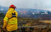A forest firefighter watches as lava flows next to houses following the eruption of a volcano in Spain
