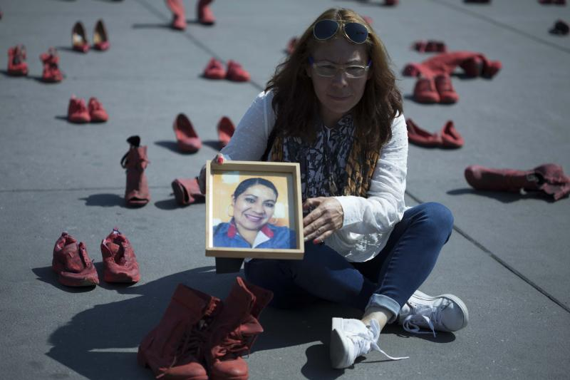 Elizabeth Machuca Campos holds the portrait of her sister Eugenia Machuca Campos amid women's red shoes placed in the Zocalo by people protesting violence against women in Mexico City, Saturday, Jan. 11, 2020. According to Elizabeth, her sister's ex-boyfriend is serving time in jail for her Oct. 2017 murder in the State of Mexico. (AP Photo/Christian Palma)