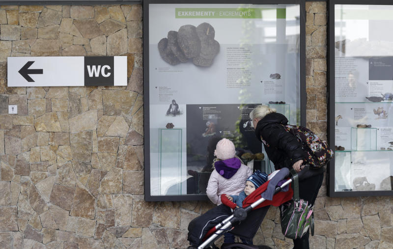 In this picture taken on Monday, May 6, 2019, visitors view an exhibition of animal excrements at the Prague Zoo, Czech Republic. The park has opened a new permanent exhibition that put on display wide range of animal feces. Placed on the outside walls of a new building with toilets, the exhibition offers information and samples from fossil turds, also known as coprolites, to the excrements of current animals of various size, shape, texture and color. (AP Photo/Petr David Josek)
