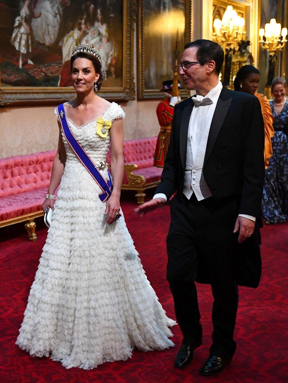 """<p><a href=""""https://www.townandcountrymag.com/style/fashion-trends/a27682334/kate-middleton-jewelry-dress-buckingham-palace-state-banquet-donald-trump/"""" rel=""""nofollow noopener"""" target=""""_blank"""" data-ylk=""""slk:Kate wore a tiered Alexander McQueen gown to a state banquet with Donald Trump"""" class=""""link rapid-noclick-resp"""">Kate wore a tiered Alexander McQueen gown to a state banquet with Donald Trump</a>. She paired the dress with the Lover's Knot Tiara, and the Queen Mother's sapphire and diamond fringe earrings.</p>"""