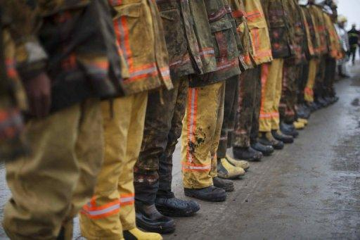 Chinese firemen prepare to leave after finishing their work extinguishing a blaze in Dalian, Liaoning province