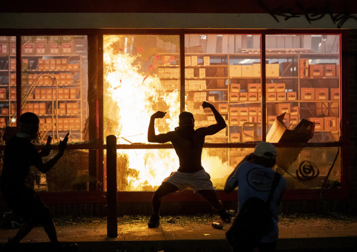Protesters stand in front of an AutoZone that was set on fire during a demonstration in Minneapolis Wednesday.was started at AutoZone. (Carlos Gonzalez/Star Tribune)