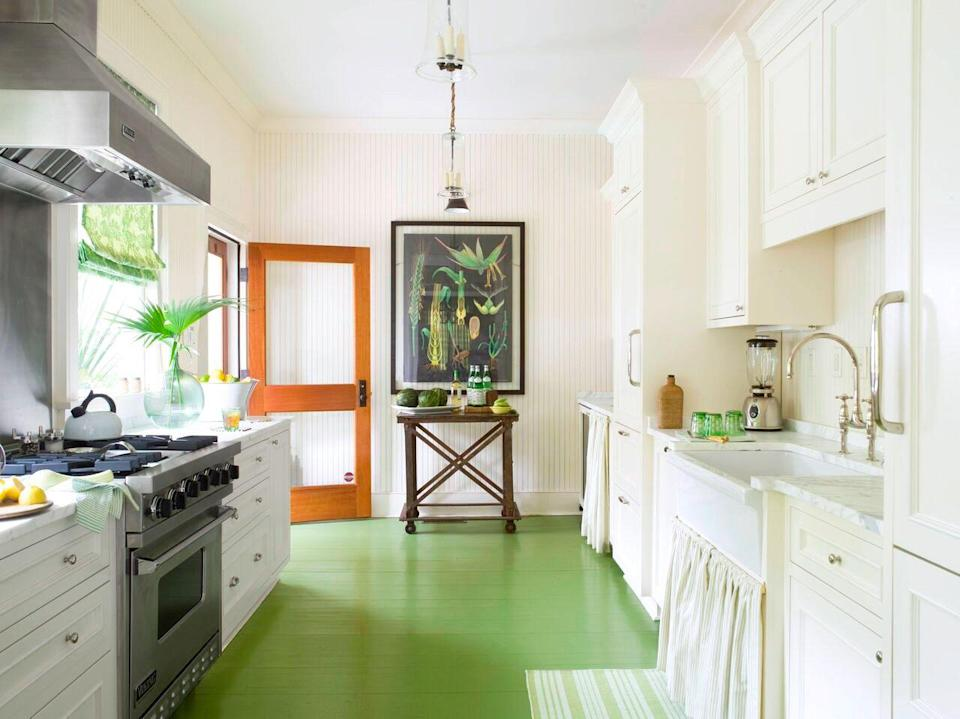 <p>In this bright kitchen , the spring green painted hardwood floors feel like a warm welcome. The framed print, linen curtains, and striped ares rug carry that sentiment throughout the space. Another important takeaway? A bar cart is probably the finishing touch you didn't know you need in a narrow kitchen without an island. </p>