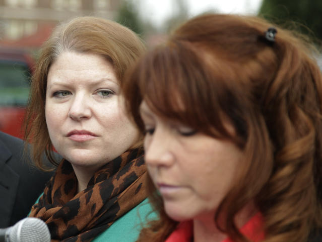 Kari Bales, left, listens as her sister, Stephanie Tandberg, right, reads a statement to reporters Tuesday, Nov. 13, 2012, outside the building housing a military courtroom on Joint Base Lewis McChord in Washington state, where a preliminary hearing ended Tuesday for Kari's husband, U.S. Army Staff Sgt. Robert Bales. Bales is accused of 16 counts of premeditated murder and six counts of attempted murder for a pre-dawn attack on two villages in Kandahar Province in Afghanistan in March of 2012. (AP Photo/Ted S. Warren)