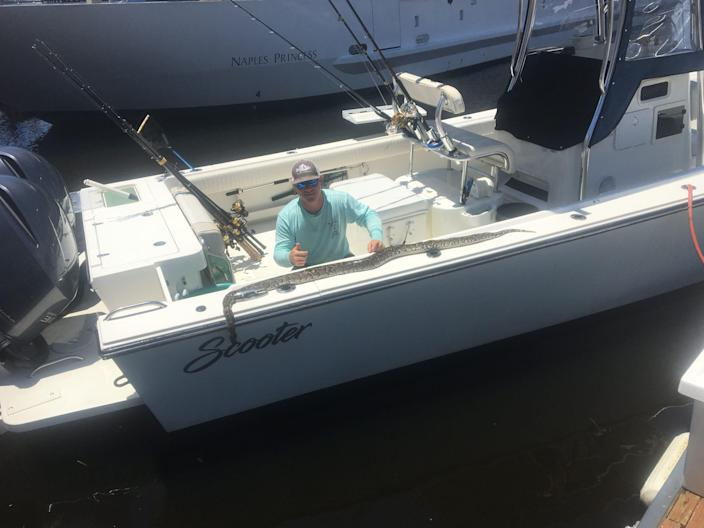 Charter captain Stephen Iannotta poses with that Burmese python that he spotted Thursday while boating in Naples Bay.