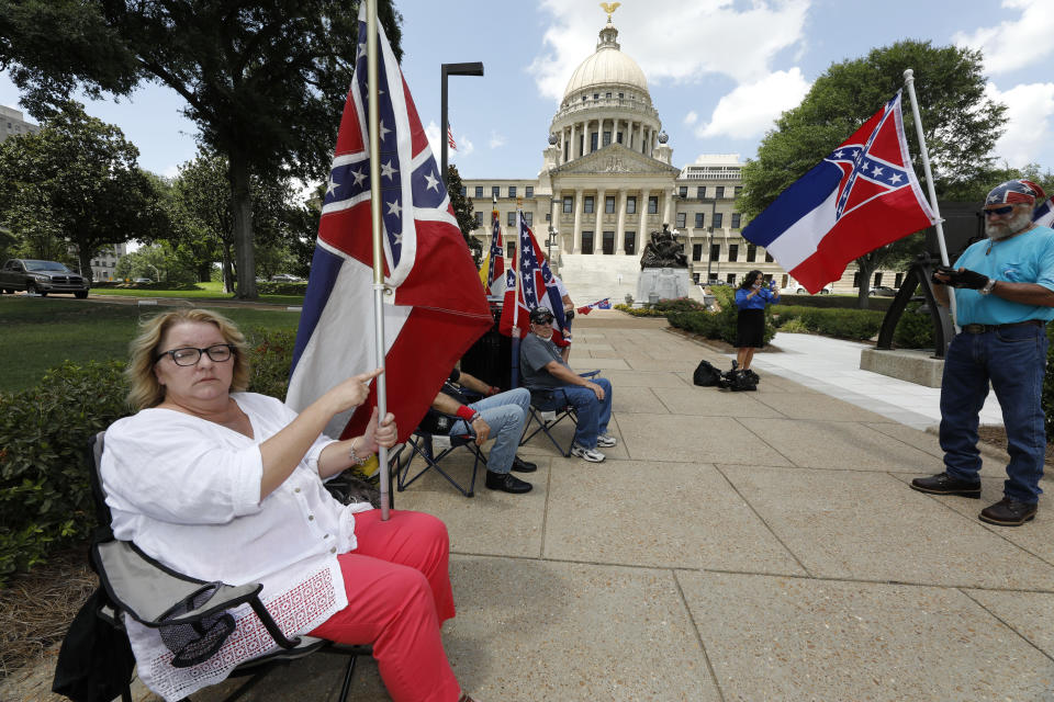 Tessa Collett of Petal, left, wants her vote to count as she supports the current flag as do other supporters standing outside the state Capitol in Jackson, Miss., Sunday, June 28, 2020. Lawmakers in both chambers are expected to debate state flag change legislation today. Mississippi Governor Tate Reeves has already said he would sign whatever flag bill the Legislature decides on. (AP Photo/Rogelio V. Solis)
