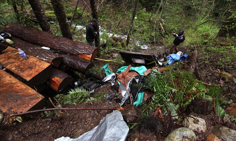 Journalists and officials peer around a multi-level bunker dug into the side of a remote ridge where murder suspect Peter Keller died days earlier, Monday, April 30, 2012, near North Bend, Wash. Keller spent eight years carving his hole in the side of the mountain, camouflaging the rugged underground bunker with ferns and sticks and stocking it with a generator and ammunition boxes sealed in Ziploc bags. Suspected in the deaths of his wife, daughter and pets last weekend, he headed there prepared for the long haul with high-powered rifles, scope and body armor. Police pumped in tear gas, called for him over bullhorns, and, after 22 hours, set off explosives along the top of the bunker Saturday. He was found dead of a self-inflicted gun shot. (AP Photo/Elaine Thompson)