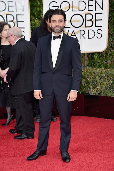 Oscar Isaac in a navy blue tuxedo with black lapels at the 73rd Golden Globe Awards.