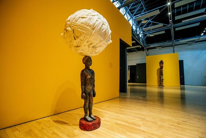 A figure of a woman balances an enormous ball of cloth on her head